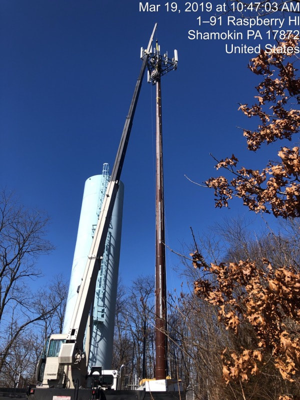 crane lifting parts to construct water tower